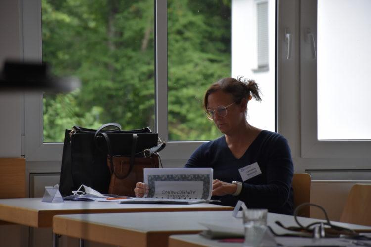 Foto: Christina Meinusch am Tisch sitzend, in einer Broschüre blätternd