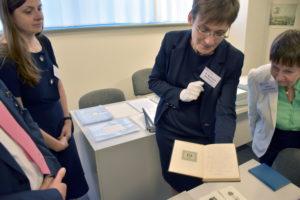 Foto: Dr. Brockmann zeigt ein Buch aus dem Dedecius Archiv