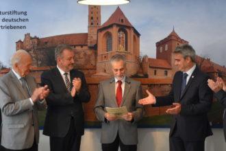 Foto: Dr. Ernst Gierlich mit BdV-Präsident Fabritius und Gratulanten